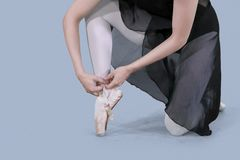 Young ballerina tying ballet shoes on studio. Closeup of a young ballerina is tying ballet shoes in the studio. Shot with gray background stock photography