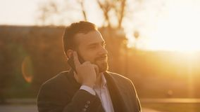 Closeup of Young bearded business man in coat talking at smartphone and making deals on street with sunlight backlit in Stock Photo