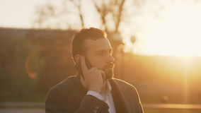 Closeup of Young bearded business man in coat talking at smartphone and making deals on street with sunlight backlit in stock video footage