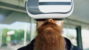 Closeup of Young bearded man using virtual reality headset for 360 VR experience and take of glasses smiling outdoors. Closeup of Young bearded man using virtual Stock Images