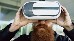 Closeup of Young bearded man using virtual reality headset for 360 VR experience and take of glasses smiling outdoors. Closeup of Young bearded man using virtual Royalty Free Stock Image