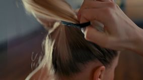 Young Lady Tying Blond Hair and Making Ponytail before Training in the Gym. CloseUp of Young Beautiful Blond Woman Tying her Hair and Making Ponytail while stock video footage