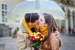 Closeup of young beautiful couple kissing under umbrella Stock Photo