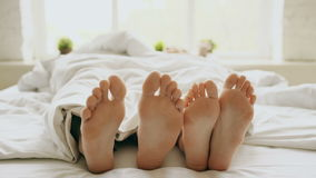 Closeup of young beautiful and loving couple play and dance their feet under blanket while wake up in bed in morning. Closeup of young beautiful and loving stock footage