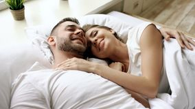 Closeup of young beautiful and loving couple talk and hug into bed while waking up in the morning. Top view of attractive men chatting his smiling wife Stock Photos