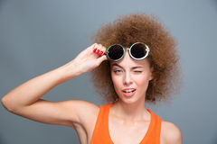 Closeup of young beautiful winking model in green sunglasses Stock Photo