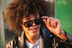 Closeup of young black man with afro hairstyle, sunny urban background royalty free stock photos