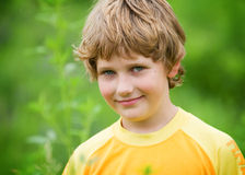 Closeup of a young boy outdoors. Young boy looking at the camera with a smile closeup outdoor shot Stock Photography