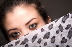 Closeup young brunette model posing with grey brown scarf covering half her face revealing beautiful eyes only, dark Stock Images