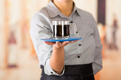 Closeup young brunette waitress wearing uniform, holding up tray containing two glasses of dark liquid using both hands Stock Photo
