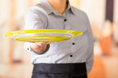 Closeup young brunette waitress wearing uniform, holding up yellow empty tray using one hand Royalty Free Stock Photos