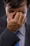 Closeup of young business man with headache. Rubbing temples Royalty Free Stock Photo