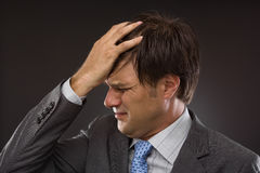 Closeup of young business man with headache. On gray Royalty Free Stock Photography