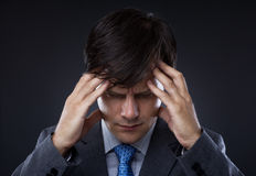 Closeup of young business man with headache. Rubbing temples Stock Photos