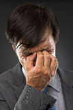 Closeup of young business man with headache. Rubbing temples Royalty Free Stock Images