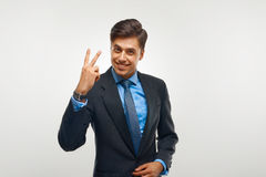 Closeup of a young business man showing showing two number. Royalty Free Stock Images