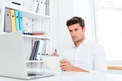 Closeup of young businessman sitting and writing in notepad. Closeup of handsome young businessman sitting and writing in notepad at workplace Stock Photos