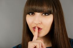 Closeup of young businesswoman making silence sign isolated on g Royalty Free Stock Image