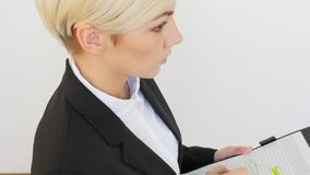 CloseUp of Young Businesswoman Writes on ClipBoard stock footage