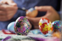 Young man decorating easter eggs. Closeup of a young cacausian man decorating some easter eggs by gluing some pieces of different papers, on a gray rustic wooden Royalty Free Stock Photo