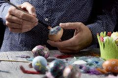 Young man decorating homemade easter eggs. Closeup of a young cacausian man decorating some homemade easter eggs by gluing some pieces of different papers, on a Royalty Free Stock Images