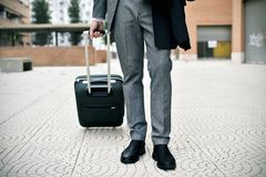 Businessman pulling a trolley case. Closeup of a young caucasian businessman in an elegant gray suit pulling a trolley by its handle in a pedestrian zone Royalty Free Stock Photos