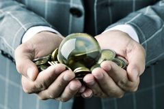 Businessman with a crystal ball and euro coins Stock Images