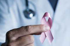 Doctor with a pink ribbon in his hand stock images