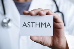 Doctor and signboard with text asthma. Closeup of a young caucasian doctor man in a white coat showing a signboard with the text asthma written in it stock photos