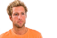 Closeup of young Caucasian male in a bright orange t-shirt. A young blonde, Caucasian, male with blue eyes in a bright orange t-shirt Royalty Free Stock Photos