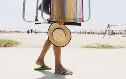 Young man carrying a beach chair. Closeup of a young caucasian man carrying a beach chair and a straw hat in his hand, going or coming back from the beach Stock Photos
