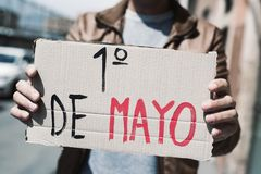 Text may day in spanish in a brown signboard. Closeup of a young caucasian man outdoors showing a brown cardboard signboard with the text 1 de mayo, may day in stock images