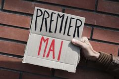 Text may day in french in a cardboard signboard. Closeup of a young caucasian man outdoors showing a brown cardboard signboard with the text premier mai, may day stock photo
