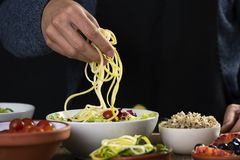 Young man preparing a buddha bowl. Closeup of a young caucasian man preparing a buddha bowl, with different ingredients, such as lettuce, cornsalad, quinoa stock photo