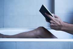 Man reading in bathtub in a mysterious atmosphere. Closeup of a young caucasian man reading a book in a bathtub, in a mysterious atmosphere, with a dramatic stock images
