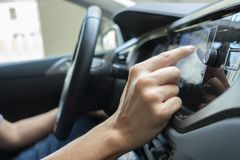 Man using the navigation system of a car. Closeup of a young caucasian man using the automotive navigation system of a car royalty free stock photography