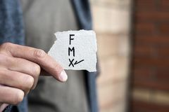 X for the third gender category. Closeup of a young caucasian person holding a piece of paper with the letters F for female, M for male and X for the third royalty free stock images