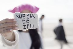 Woman with a pink hat and the text we can do it stock photography