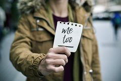 Woman showing a note with the text me too. Closeup of a young caucasian woman in the street showing a piece of paper with the text me too written in it Stock Photography