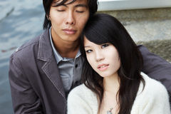 Closeup of young chinese couple on romantic date. Young Chinese beauty leaning on the shoulders of her boyfriend by river stairways Stock Photo