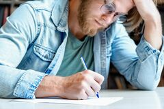 Free Closeup Young Concentrated Student Writer Hold Head Handwrite Test. Stock Images - 176977204
