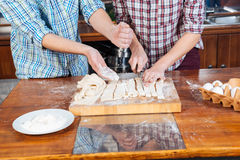 Closeup of young couple kneading dough and baking Stock Photography