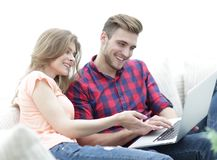 Closeup of young couple with laptop. On a light background Royalty Free Stock Photo