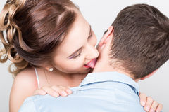 Closeup of a young couple in love, man stands with his back to the camera, she gently touches  tongue to his neck Royalty Free Stock Image
