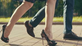 Closeup of young couple`s feet as they walk through park at sunset.  stock video