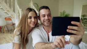 Closeup of Young cute and loving couple having video chat holding smartphone and chatting to friends sitting in bed at Royalty Free Stock Image