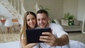 Closeup of Young cute and loving couple having video chat holding smartphone and chatting to friends sitting in bed at. Young cute and loving couple having video stock images