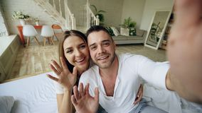 Closeup of Young cute and loving couple having video chat holding smartphone and chatting to friends sitting in bed at. Young cute and loving couple having video royalty free stock photo