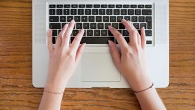 Female hands typing on laptop. Closeup of young female hands typing on laptop royalty free stock photo