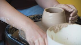 Closeup of young female potter with sponge keeping it close to rotating clay pot while shaping form of pot during work